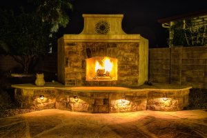 Faux stone, stucco, and lighting added to an outdoor fireplace