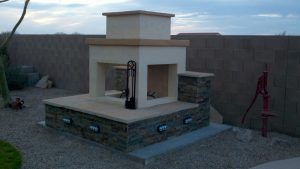 Outdoor fireplace with stacked stone, flagstone and lighting