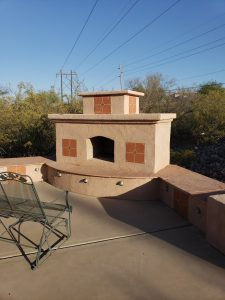 DIY outdoor fireplace with stucco and tile finish