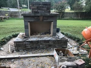 DIY outdoor fireplace backyard patio veneer construction cement mixer hearth chimney grass fence firebrick cornerstone