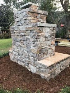 DIY outdoor fireplace veneer backyard patio mulch chimney hearth flagstone grass trees