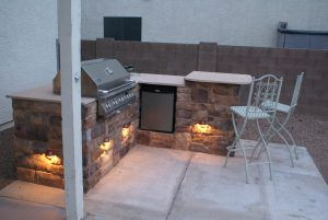 Outdoor kitchen with lighting refrigerator and bar