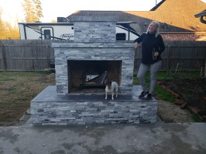 Completed DIY outdoor fireplace with owner and dog