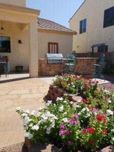 Flagstone patio red door grill kitchen flowers