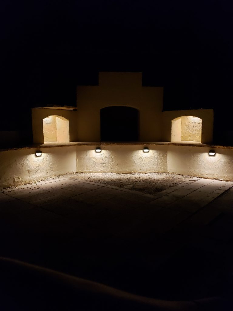 Outdoor lighting on DIY outdoor fireplace at night