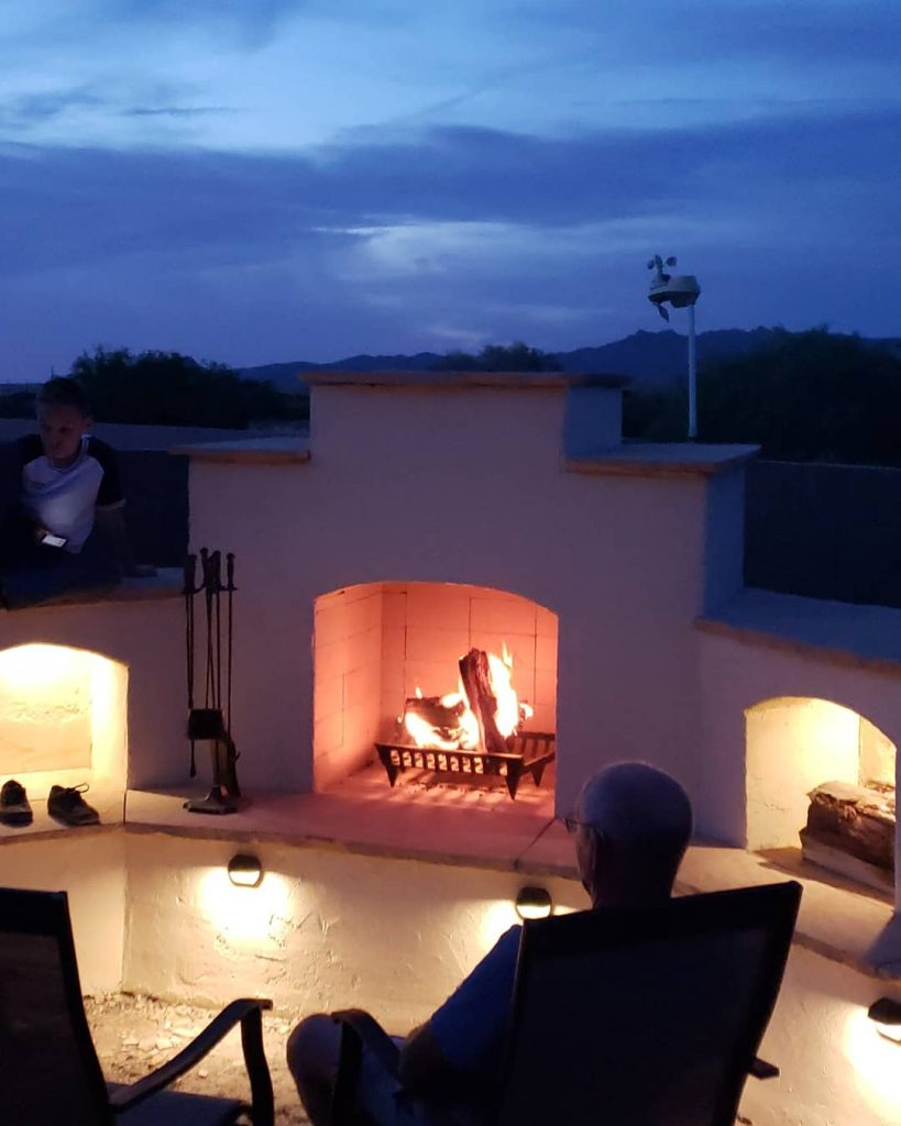 DIY outdoor backyard fireplace at night with fire