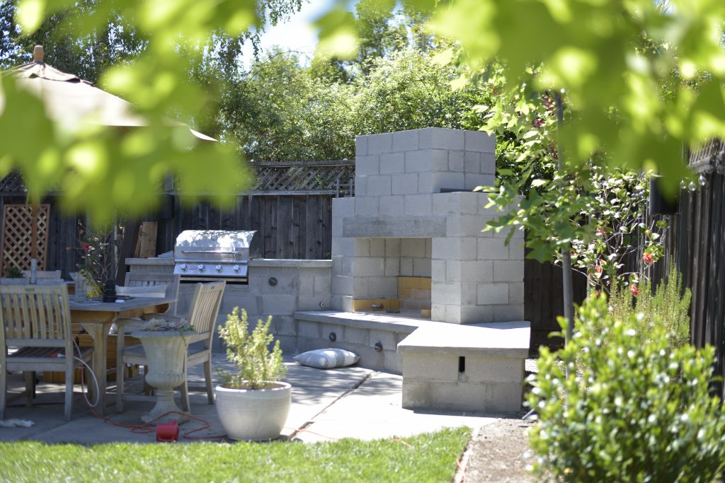 Cinder block construction outdoor fireplace and outdoor kitchen under construction in a backyard.  This fireplace is surrounded by chairs and is under trees.
