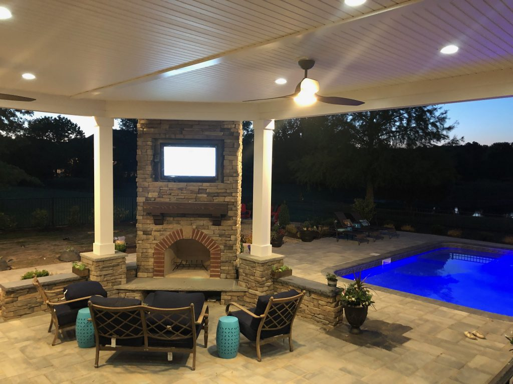 DIY outdoor fireplace built by a homeowner in a corner under a patio cover. This is surrounded by chairs and is poolside.