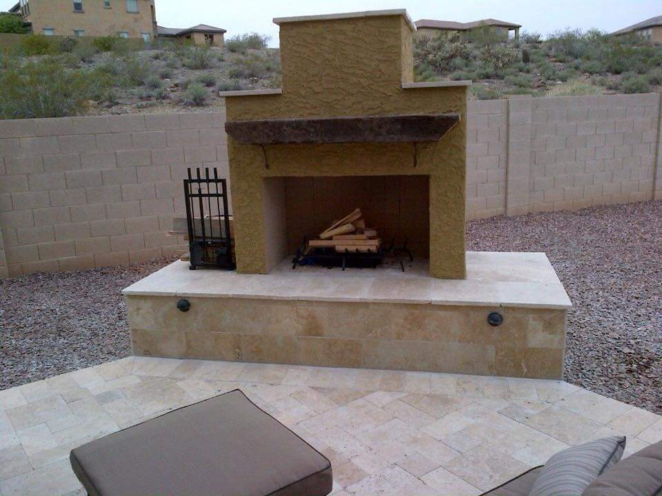 backyard outdoor DIY fireplace built on patio with travertine and stucco finish.