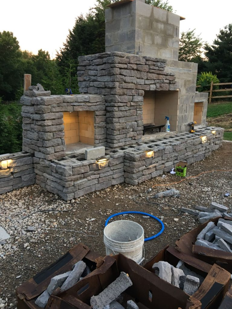 Masonry construction outdoor fireplace with storage and concrete lintels