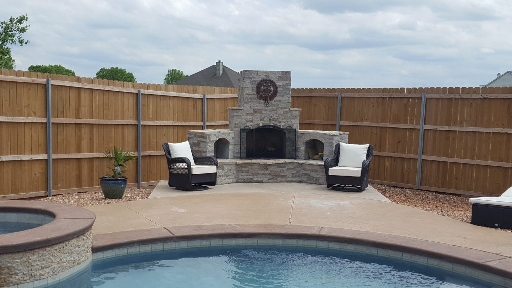 DIY outdoor fireplace built from cinderblocks and mortar covered in stone veneer.  Metal art on chimney and pool and hot tub in front of fireplace. Patio furniture and wooden fence.  Construction zone in backyard of Cholla design.
