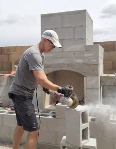 Man in white hat cutting cinderblock. Masonry DIY outdoor fireplace behind him. Diamond blade and grinder being used on construction.